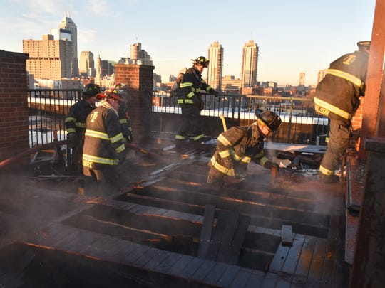 Indianapolis firefighters are shown extinguishing the fire on the roof of the Beilouny Building at 757 Mass Ave. in Downtown Indianapolis.
