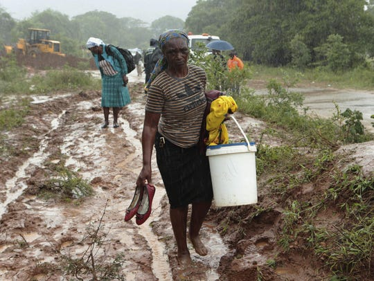 People trudge through a muddied path to safer ground