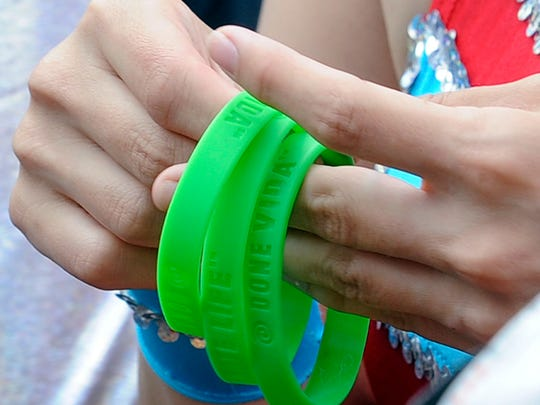 Nicole Taugner of Plover, a member of the Wisconsin Rapids Aqua Skiers Show Ski Team, hands out green Donate Life wristbands to members of the Aqua Skiers on Thursday, prior to the team competing in the 48th annual Wisconsin State Water Ski Show. Taugner's father, Lynn Bardele, who was part of the Shermalot Water Ski Show Team, died in December. He was an organ donor. Visit wisconsinrapidstribune.com for a photo gallery of the Shermalot Water Ski Show Team competing.