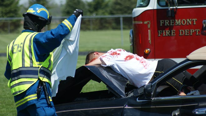 In this mock crash at Ross High School, a Sandusky County EMS responder drapes a white blanket over a 'dead' passenger.