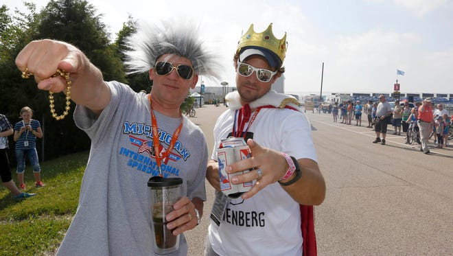 Roger Curtis, left, President of MIS, is with a fan known as King of the Infield, before a race in June 2014.