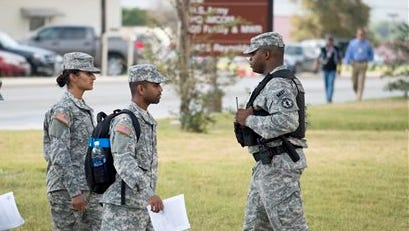 Soldiers walk past a military police officer, right, patrolling the perimeter of the US Army IMCOM HQ building prior to the Article 32 preliminary hearing to determine if Army Sgt. Bowe Bergdahl will be court martialed, Thursday, Sept. 17, 2015, at Fort Sam Houston in San Antonio. Bergdahl, who left his post in Afghanistan and was held by the Taliban for five years, is charged with desertion and misbehavior before the enemy. (AP Photo/Darren Abate)