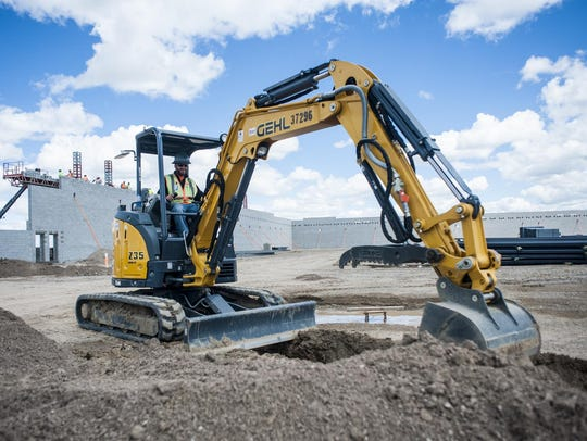 Mark Grimes operates a mini excavator inside what will