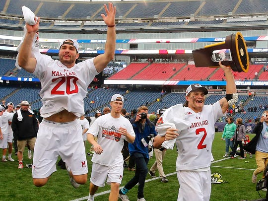 May 29, 2017; Foxborough, MA, USA; Maryland midfielder Nick Manis (20) leaps in the air as attackmen Colin Heacock (2) hoists the trophy after their 9-6 win over Ohio State in the NCAA Championship game at Gillette Stadium. Mandatory Credit: Winslow Townson-USA TODAY Sports