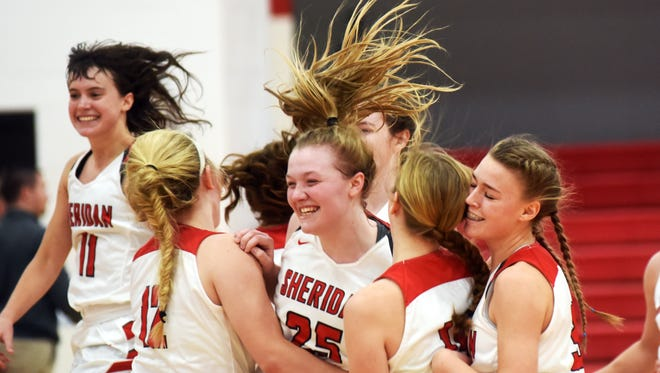 Sheridan players celebrate after holding on for a 57-55 win against visiting Tri-Valley on Saturday at Glen Hursey Gymnasium.