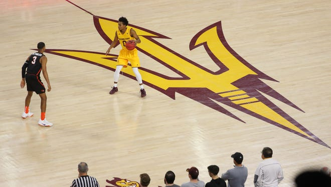 ASU's Tra Holder (0) dribbles near the Sun Devil logo against Pacific's Miles Reynolds (3) during the second half at Wells Fargo Arena on December 22, 2017 in Tempe, Ariz.