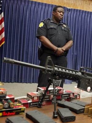 In this Oct. 16, 2012 photo, Fresno, Calif., Police chief Jerry Dyer, at podium, gives a news conference with deputy police chief Keith Foster, left, and Lt. David Newton in front of a large cache of weapons, money and marijuana seized in a bust. Foster, 51, was arrested for conspiracy to distribute and/or possess with the intent to distribute oxycodone, heroin and marijuana, the FBI said in a statement Thursday, March 26, 2015. Foster aand three other Fresno residents were arrested as result of a yearlong joint investigation by the FBI and ATF that involved wiretaps and surveillance, the FBI said.
