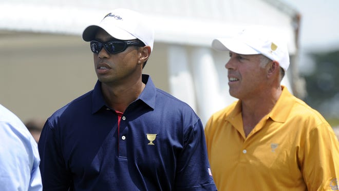 In this Nov. 17, 2011 file photo, Tiger Woods, left, of the U.S. team and his former caddie Steve Williams stand on the first tee during the first round of the Presidents Cup at Royal Melbourne Golf Course, in Melbourne, Australia.