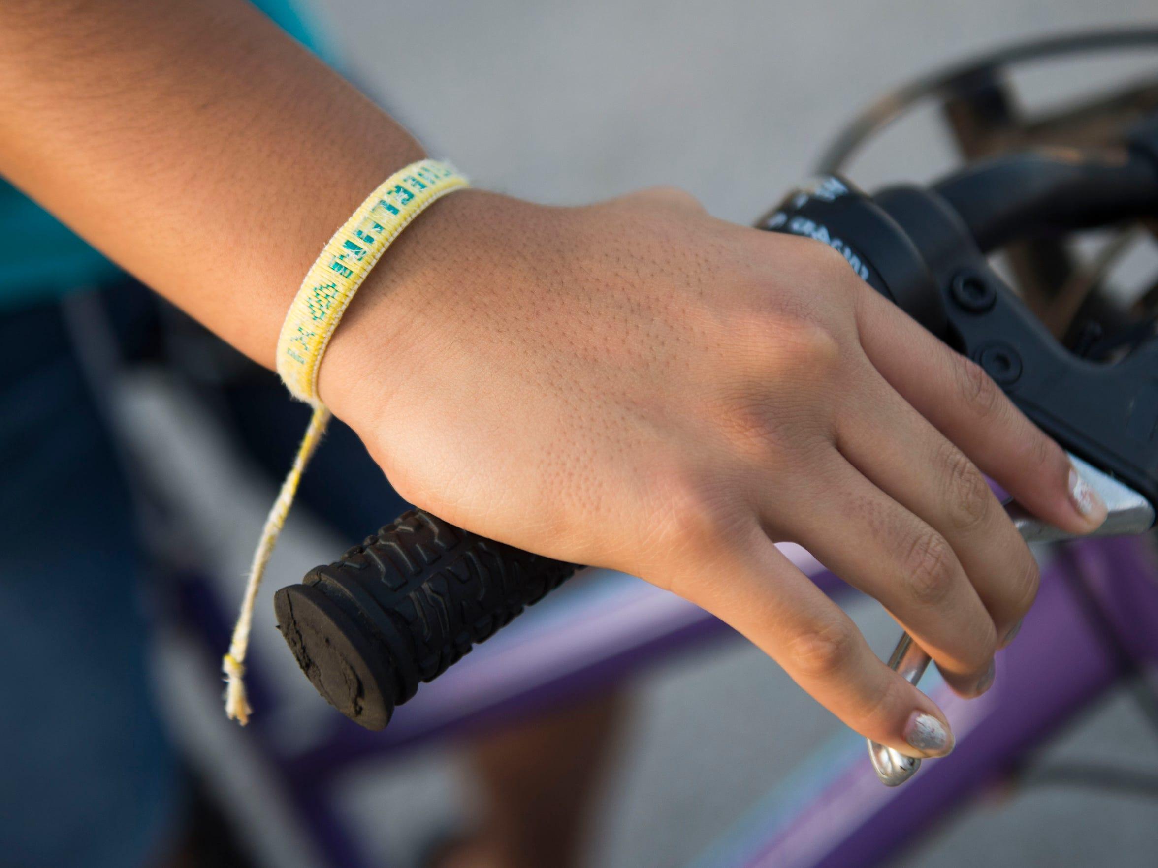 Sheryln Librado, 11, wears a bracelet her father made