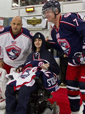 """Doug Hood/Staff Photographer Mikey Nichols is greeted by Boomer Esiason (7) and Craig Carton of radio station WFAN during a ceremony prior to the start of last year?s benefit hockey game. This year?s game with be played Saturday at the Ice World sports complex in Middletown. Mikey Nichols is greeted by Boomer Esiason (7) and Craig Carton (8) of WFAN radio during a ceremony prior to the start of a Feb. 7 benefit hockey game. The """"Mikey Strongâ"""" NHL alumni game was conducted at the Ice World sports complex in Middletown."""