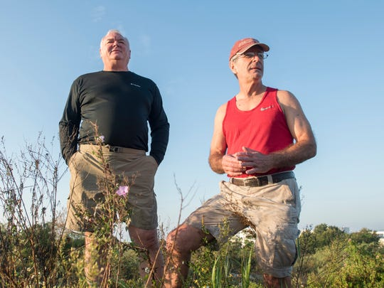 Jerry Holzworth, left, and Dan Lindemann check out the view from the hill above Bruce Beach in Pensacola on Tuesday, November 7, 2017.  A fish hatchery is proposed to be built on the Bruce Beach property.