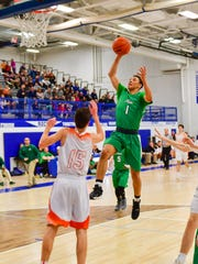 Novi's Trendon Hankerson (1) goes in for the slam dunk with Northville's Mark Grimes (15) underneath the basket.