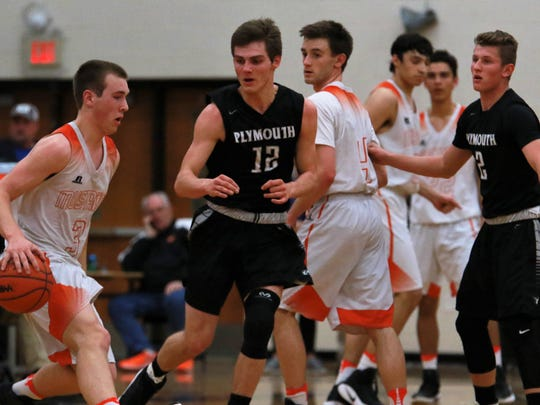 Northville's Jake Justice (3) tries to dribble past Plymouth's Joey Robb (12) during Wednesday's district game. Also shown are Kevin Morrissey (4) of the Mustangs and Zach Beadle (2) of the Wildcats.