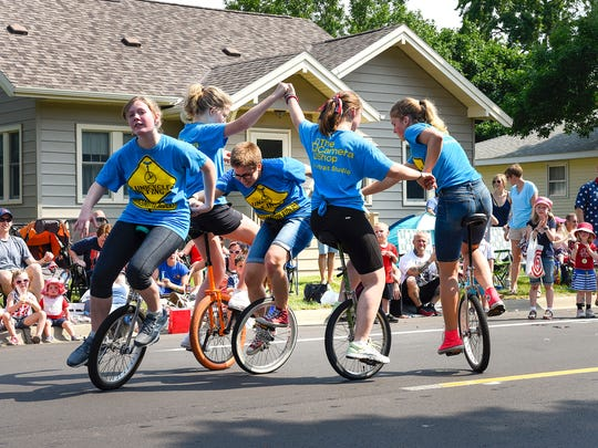 The Ringsmuth Riders Unicycle Team perform the pretzel maneuver during the Church of St. Joseph Parish Festival parade Tuesday, July 4, in St. Joseph.