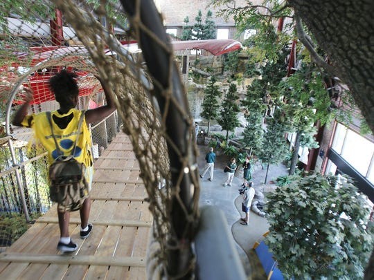 "A camper with Franklin-Wright Settlements crosses the rope bridge at the DNR's new Outdoor Adventure Center at 1801 Atwater in downtown Detroit following a ribbon-cutting ceremony  July 16, 2015.  The 41,000-square-foot Center aims to bring ""Up North Downtown"" by offering ""indoor , hands-on, interactive exhibits and experiences about Michigan's out-of doors, to an urban audience."""