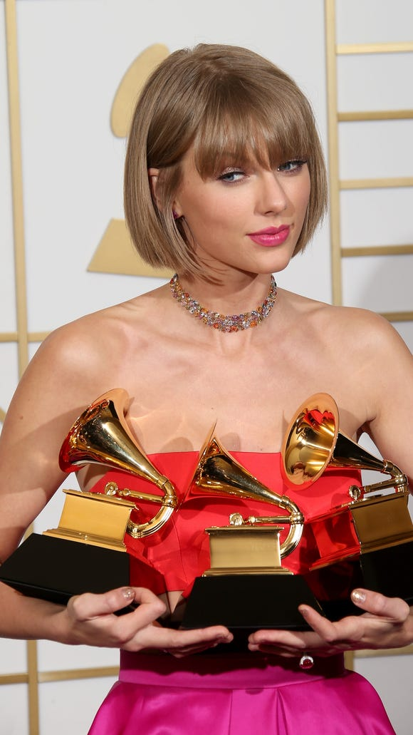 Taylor Swift, holding her awards for Album of the Year