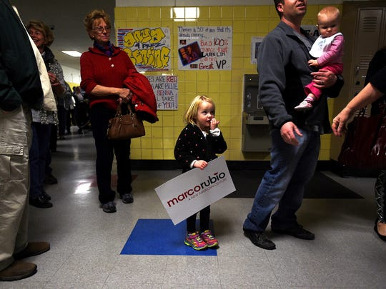 Three-year-old Ella Harsh waits in line to register with her dad Troy, right, during the Republican Caucus at Reno High School in Reno on Feb. 23, 2016.