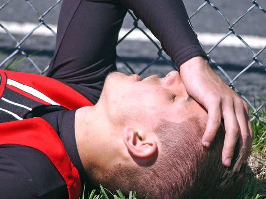 Riverheads' Ryan Rathburn has his hand to his head and collects himself before running the boys 400 meter run during a track meet at Riverheads High School in 2005. Rathburn says he dealt with the after effects of his previous concussions all the time during track and even recalls a seizure at practice once.