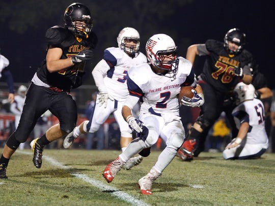 Tulare Western's David Alcantar carries the football against Tulare Union in last season's Bell Game.