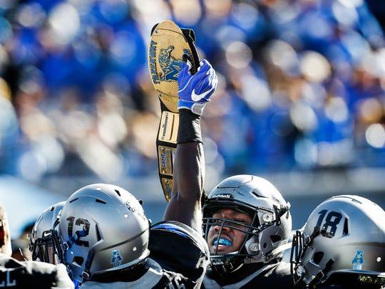 Memphis teammates celebrate with a wrestling belt after