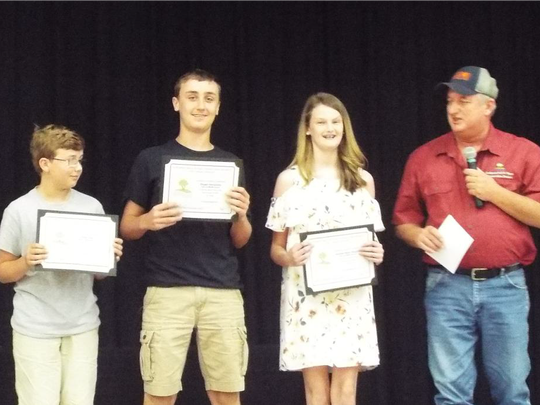 Starr-Iva Middle School winners (left to right) Ethan Hall (3rd Place), Regan Hendricks (2nd Place) and Audree Hope Vaughn (1st Place) with Commissioner Tim Kelley.