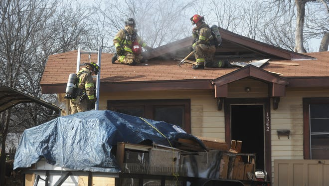 Firefighters work on a fire on the attic of an unoccupied house, undergoing renovations in the 1300th block of Elm Street. The cause of the blaze is still under investigation.