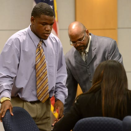 Suspended Escambia High School football player Terik Miller sits down with his parents Kevin and Cynthia on Wednesday in front of Judge Ross Goodman during an evidentiary hearing.