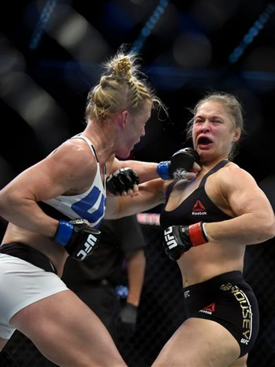 Holly Holm, left, punches Ronda Rousey during their UFC 193 bantamweight title fight in Melbourne, Australia, on Sunday. Holm pulled off a stunning upset victory over Rousey in the fight, knocking out the women's bantamweight champion in the second round with a powerful kick to the head Sunday.