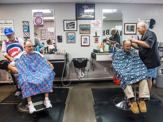 Barbers Peter Apostle, left, and Paul Tamborino give haircuts to clients at Paul's Barber Shop in Bonita Springs on March 20.