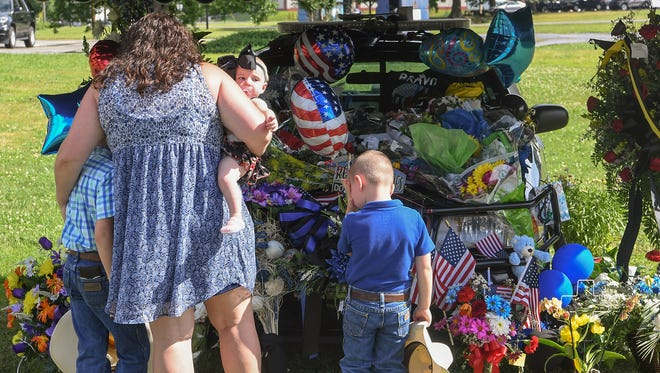 Kalyna McGee holds her daughter Lainey near her two sons Jake, left, and Eli, right, visiting a memorial with the cruiser of Devin Hodges, the Anderson County Sheriff's Office deputy who was fatally injured during a training exercise Thursday, on Monday before going to the wake at the Civic Center of Anderson.
