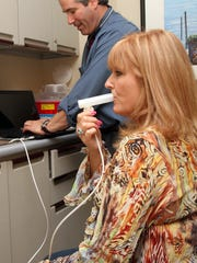 Dr. Jeffrey Lederman gives a lung screening test to patient Gail Carmichael of Manalapan.