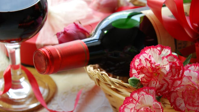 a glass of red wine and a bottle with carnation flowers in basket for celebrating occasions.