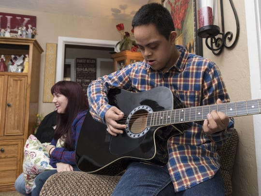 Adopted son Joey Bonds plays the guitar he got for Christmas while Amber Gates (the Bond's first adopted child) talks with family on Wednesday, January 11, 2017.