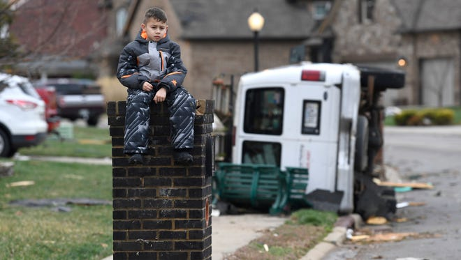 Gio Rodriguez, 8, sits outside his home as his parents clean up debris Sunday morning after a fierce storm hit Saturday, Feb. 24, 2018, in the Farmington subdivision in Clarksville, Tenn.