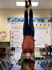 Taylor Miller, nee Keeker, does a handstand in her second-grade classroom at Keizer Elementary School.