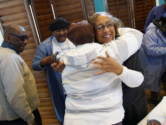 Cynthia Oates embraces a fellow 1953 Howard High classmate at class luncheon.