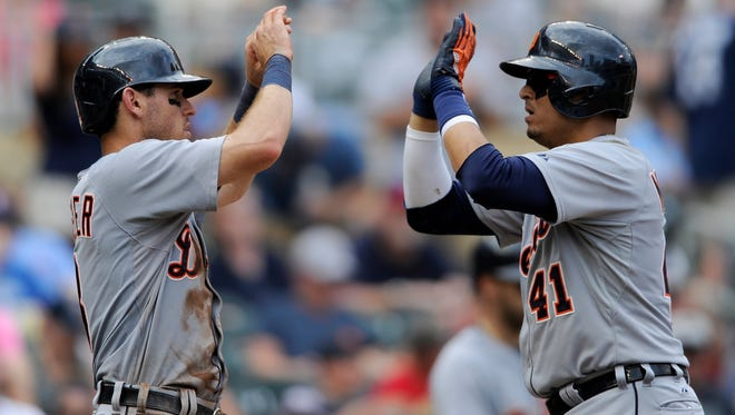 Ian Kinsler and Detroit Tigers teammate Victor Martinez, right, celebrate against the Minnesota Twins on Aug. 24, 2014, at Target Field in Minneapolis.