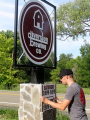 Dutch Blokzyl adds hours to the sign in front of Diversion Brewing Co. on Wyncook Creek Road in the Town of Chemung.