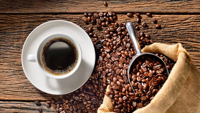 Cup of coffee and coffee beans on wooden table.