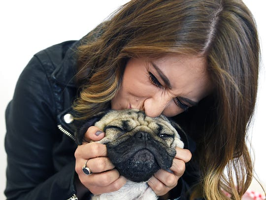 Leslie Mosier kisses her dog, Doug the Pug, in her