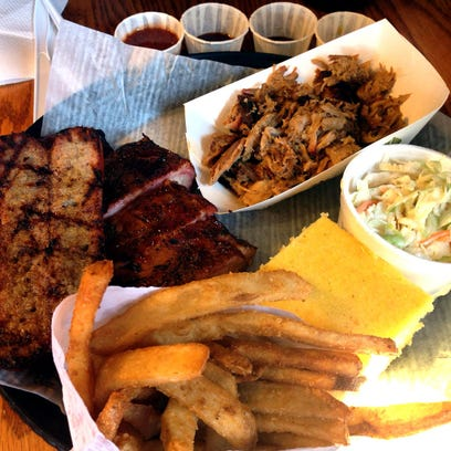 The Jack's Sampler ($17.99), features Kansas City-style barbecue, including pork ribs, a smoked Italian sausage, pulled pork, fries, honey buttered corn bread and coleslaw at Jimmy Jack's Rib Shack in Iowa City.