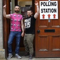 Partners Adrian, left and Shane, arrive to cast their votes at a polling station in Drogheda, Ireland, on May 22.