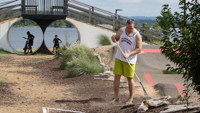 Local BMX rider Toby Duncan volunteers his Thursday, July 23, 2020, morning to clean the Riverfront bike tracks of debris using a rake and broom before taking his bike out.