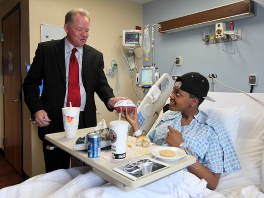 UofL coach Bobby Petrino presents an autographed football to Nautica Fielder, 19, a patient at Kosair Children's Hospital. June 19, 2014