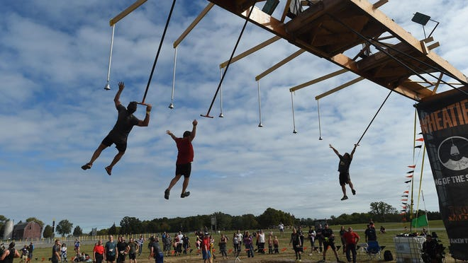 Participants take part in the King of the Swingers obstacle during the Tough Mudder at Michigan International Speedway in Brooklyn, Mich., Sunday, Sept. 27, 2015.