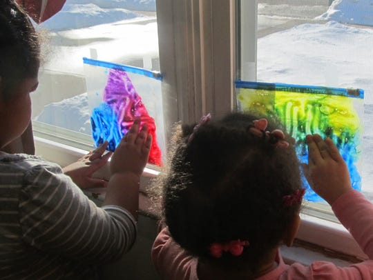 Angelia and Cera show off how to play with mess-free finger paint.