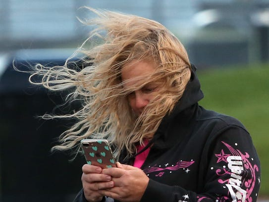 Carrie McClellan, of Bremerton, checks her phone as her hair flies about in the wind at Silverdale Waterfront Park on Monday.