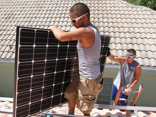 Two Fafco Solar employees take solar panels onto the roof of a Naples home in 2015.