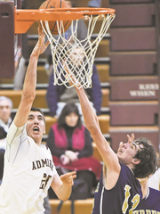 Arlington High School's Brendan Sunday, left, goes to the basket as Our Lady of Lourdes' Luke Timm defends during a February 2015 game.