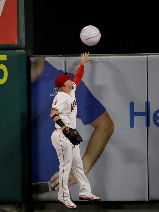 Los Angeles Angels' Kole Calhoun tosses an an inflatable ball over the fence during the third inning of a baseball game against the Toronto Blue Jays, Friday, April 21, 2017, in Anaheim, Calif. (AP Photo/Jae C. Hong)